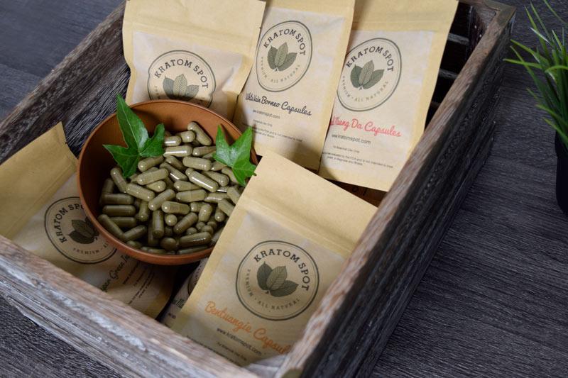 Five Kratom Spot bags surrounding a bowl of Kratom capsules