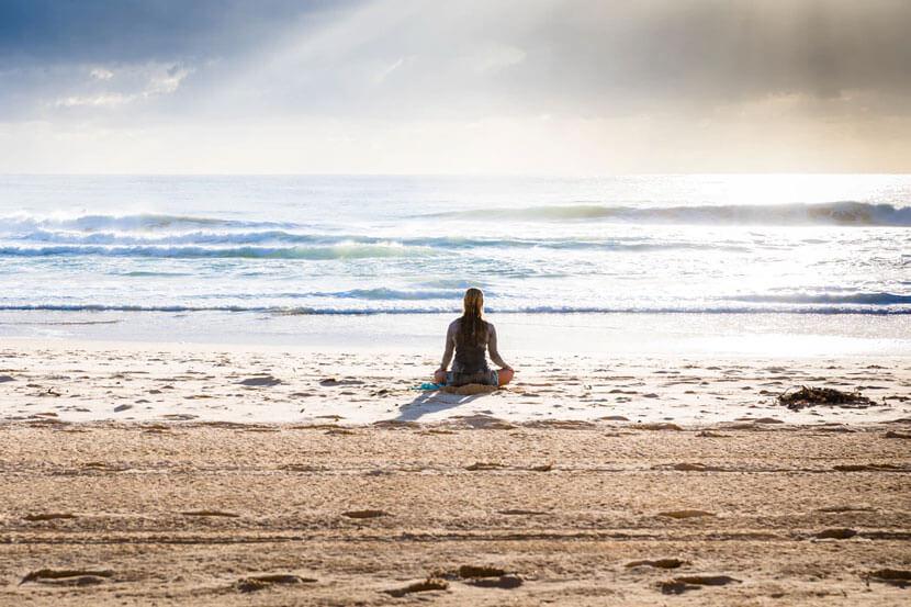 A woman on a beach meditating